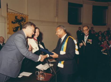 In 1982 krijgt de Senegalees Amadou-Mahtar M'Bow, hoofd van UNESCO, het 1ste Gentse eredoctoraat in de ontwikkelingssamenwerking, op voordracht van het ISVO. Op de achtergrond rechts promotor William De Coster (© Universiteitsarchief Gent, FA_04_018).