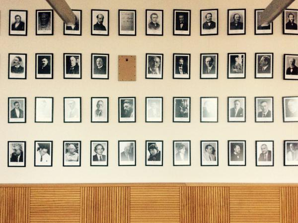 In de eregalerij van decanen in de faculteitszaal Letteren & Wijsbegeerte hangt ook taalkundige Josué De Decker, docent aan de collaborerende Vlaamse Hogeschool. Dat is niet naar de zin van het Comité voor Vaderland en Civisme.