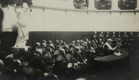 Rector Peter Hoffmann speecht in de Aula op de openingszitting van de Vlaamse Hogeschool op 24 oktober 1916. Op de achtergrond kijkt Minerva toe  (Collectie Universiteitsbibliotheek Gent)